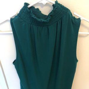 Emerald green sleeveless blouse with mock neck.